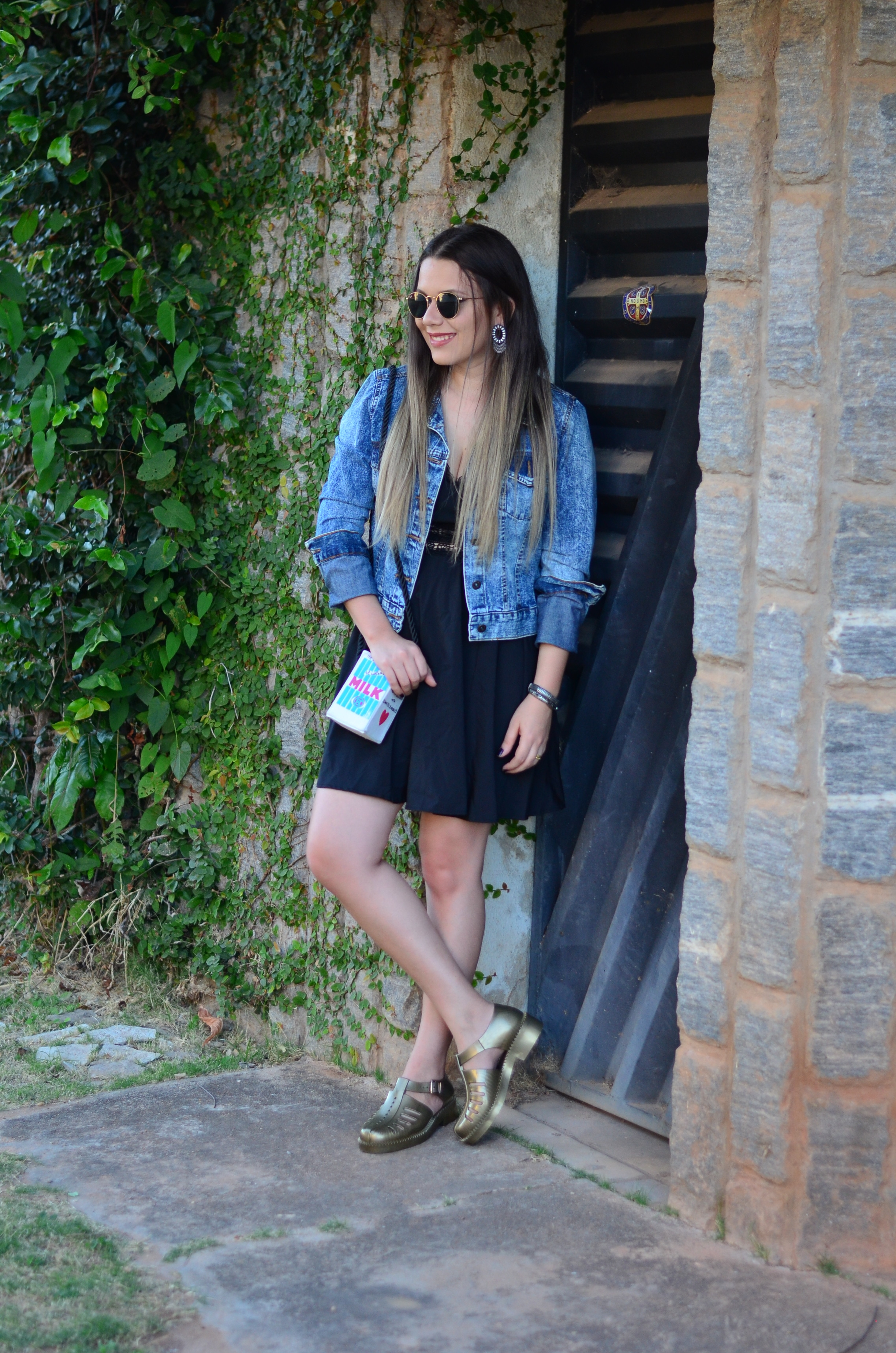 look melissa aranha bronze, vestido preto, jaqueta jeans e bolsa caixa de leite